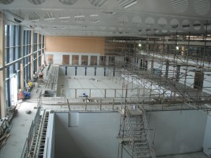 View of the new pool from the first floor, from the foreground is the small pool which will have a moveable floor, a larger 6 lane pool and the storage units at the back wall.